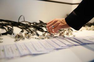 Hand greift zu Teilnehmerbadges der 1. ECON Customer Conference 2019 im Bauwerk Hafen