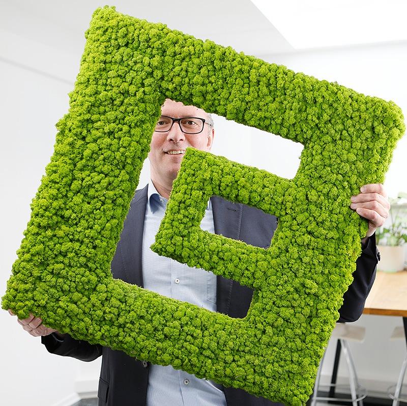 HP Olbrück Geschäftsführer ECON Application GmbH hält das Logo von ECON