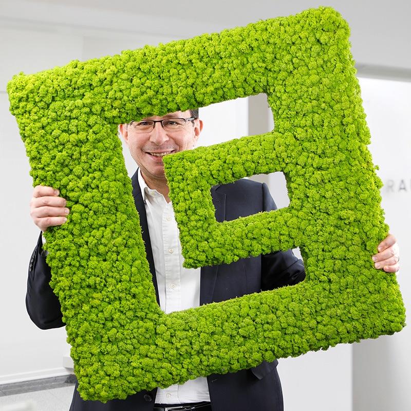Hakan Baran Geschäftsführer ECON Application GmbH hält das Logo von ECON
